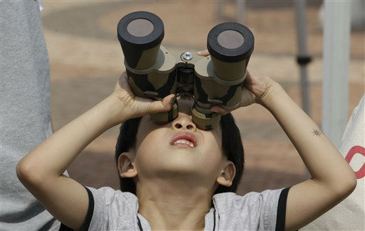 A young boy uses a pair of binoculars with special filters, to observe the transit of Venus at the National Science Museum in Gwacheon, south of Seoul, South Korea, Wednesday, June 6, 2012. From the U.S. to South Korea, people turned their attention to the daytime sky on Tuesday and early Wednesday in Asia to make sure they caught the rare sight of the transit of Venus. The next one won&#39;t be for another 105 years. &#40;AP Photo&#47;Lee Jin-man&#41; <span class=meta>(AP Photo&#47; Lee Jin-man)</span>