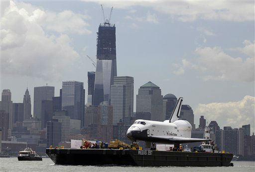 The space shuttle Enterprise passes lower Manhattan and One World Trade Center, under construction as it makes the final leg of its journey by barge to its new  home on the flight deck of the Intrepid Sea, Air &amp; Space Museum. Wednesday, June 6, 2012. The U.S. space agency, NASA, ended its shuttle program last year. &#40;AP Photo&#47;Richard Drew&#41; <span class=meta>(AP Photo&#47; Richard Drew)</span>