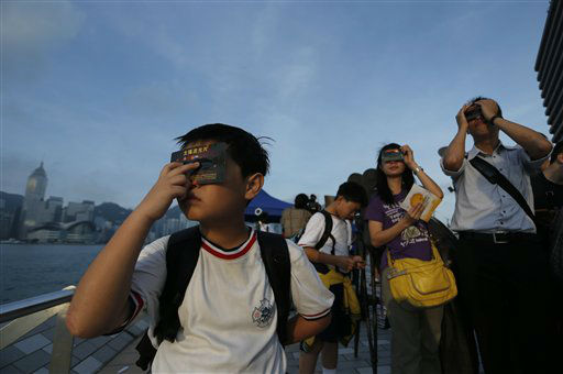 Hong Kong stargazers use special sunglasses to observe the transit of Venus  along the Victoria Habour in Hong Kong Wednesday, June 6, 2012. Stargazers around the world are setting up special telescopes and passing out cardboard eclipse glasses to view the once-in-a-lifetime celestial cameo of Venus passing in front of the sun. &#40;AP Photo&#47;Vincent Yu&#41; <span class=meta>(AP Photo&#47; Vincent Yu)</span>