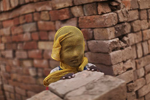 A Pakistani boy who lives near by a brick factory, covers his face with a scarf to avoid a sand storm, on the outskirts of Islamabad, Pakistan, Wednesday, June 6, 2012. &#40;AP Photo&#47;Muhammed Muheisen&#41; <span class=meta>(AP Photo&#47; Muhammed Muheisen)</span>
