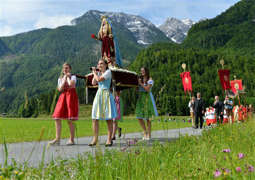 Young women, wearing traditional dresses, carry a statue of Virgin Mary during a Corpus Christi procession, in St. Martin near  Lofer in the Austrian province of Salzburg on Thursday, June 7, 2012. &#40;AP Photo&#47;Kerstin Joensson&#41; <span class=meta>(AP Photo&#47; Kerstin Joensson)</span>