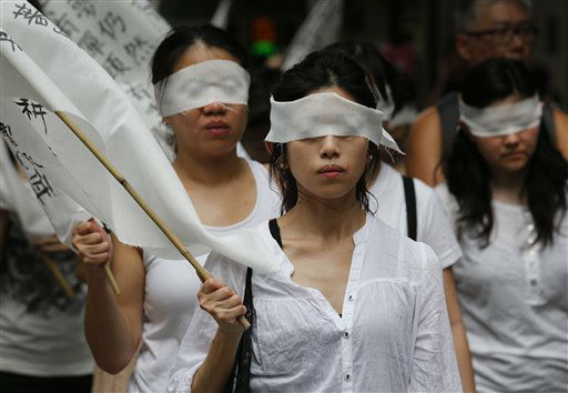 Protesters wear white dresses and cover eyes with white clothes to show their own expression to mourn for the death of Chinese labor activist Li Wangyang during a protest march in Hong Kong, Sunday, June 10, 2012. Li, imprisoned for two decades, died in a hospital Wednesday one year after being released from jail, and a relative raised doubt on the official explanation that he had hanged himself. The activist had advocated for independent labor unions in central China&#39;s Hunan province and was caught in the sweeping nationwide crackdown on all forms of dissent after the Tiananmen Square democracy protests were quashed in 1989. &#40;AP Photo&#47;Vincent Yu&#41; <span class=meta>(AP Photo&#47; Vincent Yu)</span>