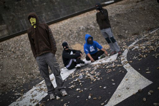 Masked miners sit on the road as they block the traffic in Cinera, near Leon, Spain, Monday, June 11, 2012. Strikes, road blockades, and mine sit-ins continue as 8,000 mineworkers at over 40 coal mines in northern Spain continue their protests against government action to cut coal subsidies. &#40;AP Photo&#47;Emilio Morenatti&#41; <span class=meta>(AP Photo&#47; Emilio Morenatti)</span>