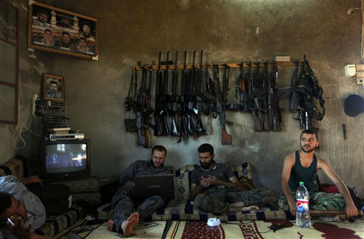 "<div class=""meta ""><span class=""caption-text "">Free Syrian Army fighters sit in a house on the outskirts of Aleppo, Syria, Tuesday, June 12, 2012.  On Tuesday, Syrian forces pelted the eastern city of Deir el-Zour with mortars as anti-government protesters were dispersing before dawn Tuesday, killing several people, activists said. The offensives were part of an escalation of violence in recent weeks that has brought more international pressure on President Bashar Assad's regime faces over its brutal tactics against the opposition. The U.N. accused the government of using children as human shields in a new report. (AP Photo) (AP Photo/ Anonymous)</span></div>"