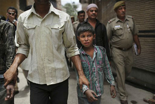 A young Indian bonded child laborer cries as he is walked away after being rescued during a raid by workers from Bachpan Bachao Andolan, or Save the Childhood Movement, at a garment factory in New Delhi, India, Tuesday, June 12, 2012. Raids on factories in the Indian capital revealed dozens of migrant kids hard at work Tuesday despite laws against child labor. Police rounded up 26 children from three textiles factories and a metal processing plant, but dozens more are believed to have escaped. Those captured had all come to New Delhi from the states of Bihar and Uttar Pradesh. &#40;AP Photo&#47;Kevin Frayer&#41; <span class=meta>(AP Photo&#47; Kevin Frayer)</span>