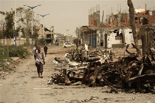 A Yemeni man walks past cars destroyed during fighting with al-Qaida militants in the city of Zinjibar, Yemen, Thursday, June 14, 2012. Airstrikes and clashes intensified in southern Yemen on Wednesday as army troops followed major victories with more pressure on al-Qaida militants holding small towns, according to tribal and military officials. The attacks came a day after Yemeni forces regained control of two major al-Qaida strongholds, Jaar and Zinjibar, which were in the hands of the militants for more than a year. &#40;AP Photo&#47;Hani Mohammed&#41; <span class=meta>(AP Photo&#47; Hani Mohammed)</span>