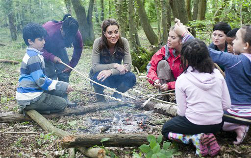Britain&#39;s Duchess of Cambridge, centre, sits with children round a camp fire during a visit to the Expanding Horizons Primary School Scheme taking part in various outdoor activities at Widehorizons&#39; Margaret McMillan House in Wrotham, England, Sunday June 17, 2012.  The Duchess of Cambridge looked comfortable today as she mucked in with children from inner-city backgrounds while they built tent shelters and cooked over campfires, developing their confidence and teamwork skills. &#40;AP Photo &#47; David Parker&#41; <span class=meta>(AP Photo&#47; David Parker)</span>
