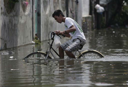 "<div class=""meta ""><span class=""caption-text "">A Filipino pedals his bicycle along a flooded street in suburban Malabon, north of Manila, Philippines, Monday June 18, 2012. Heavy rains triggered floods in several areas in the metro forcing some schools to suspend classes in the morning as powerful typhoon Guchol exits the country towards southern Japan. (AP Photo/Aaron Favila) (AP Photo/ Aaron Favila)</span></div>"