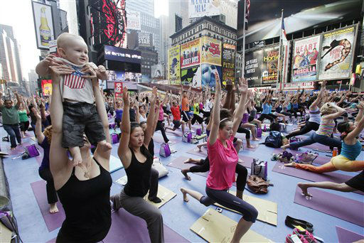 Ten-month-old Leo Erichsen is held up by his mother, Tatjana Eres of Denmark, as she joins thousands of yoga enthusiasts for a class in New York&#39;s Times Square to mark the summer solstice, Wednesday, June 20, 2012. Temperatures are expected to be near 100 degrees &#40;37C&#41; Wednesday. &#40;AP Photos&#47;Mark Lennihan&#41; <span class=meta>(AP Photo&#47; Mark Lennihan)</span>