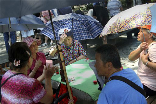 Card players try to keep cool with hats and umbrellas at Columbus Park in New York, Wednesday, June 20, 2012. The National Weather Service has forecast potentially record-breaking temperatures just as the season officially begins Wednesday, the summer solstice and longest day of the year. &#40;AP Photo&#47;Seth Wenig&#41; <span class=meta>(AP Photo&#47; Seth Wenig)</span>