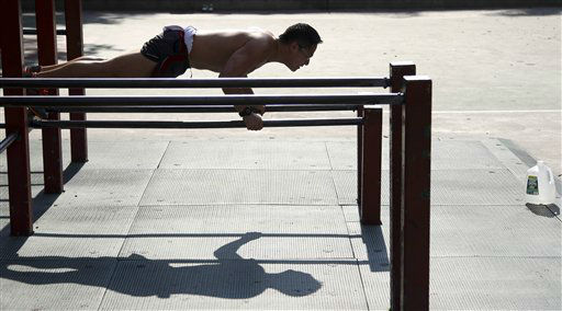 A man does push-ups on a playground at Columbus Park in New York, Wednesday, June 20, 2012. The National Weather Service has forecast potentially record-breaking temperatures just as the season officially begins Wednesday, the summer solstice and longest day of the year. &#40;AP Photo&#47;Seth Wenig&#41; <span class=meta>(AP Photo&#47; Seth Wenig)</span>