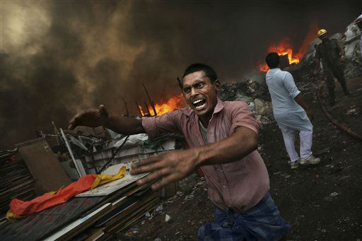 "<div class=""meta ""><span class=""caption-text "">An Indian shouts for water as a shanty town is engulfed in flames in New Delhi, India, Friday, June 22, 2012. A fire swept through a slum in the Indian capital on Friday, destroying hundreds of shanties where residents had collected scrap plastic and rubber for resale. No one was reported injured or killed, fire department chief A.K. Sharma said. (AP Photo/Kevin Frayer) (AP Photo/ Kevin Frayer)</span></div>"