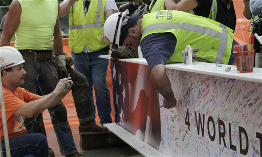 "<div class=""meta image-caption""><div class=""origin-logo origin-image ""><span></span></div><span class=""caption-text"">A construction worker signs the ceremonial last beam before it is hoisted to the top of Four World Trade Center, Monday, June 25, 2012. The 72-floor, 977-foot tower is scheduled to open late next year. It's expected to be the first tower completed on the 16-acre site since the 9/11 attacks. (AP Photo/Mark Lennihan) (AP Photo/ Mark Lennihan)</span></div>"