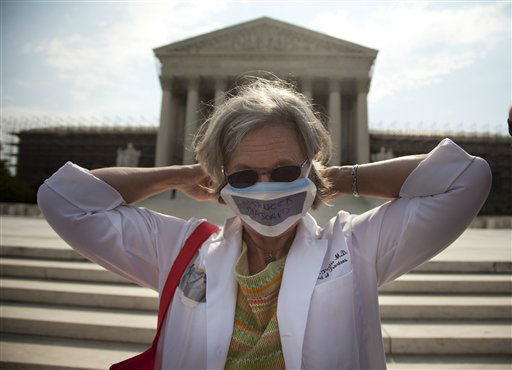 In this photo taken, Monday, June 25, 2012, Carol Paris of Leonardtown, Md. demonstrates outside the Supreme Court in Washington. On Thursday the Supreme Court will deliver their ruling on President Barack Obama&#39;s health care package. &#40;AP Photo&#47;Evan Vucci&#41; <span class=meta>(AP Photo&#47; Evan Vucci)</span>
