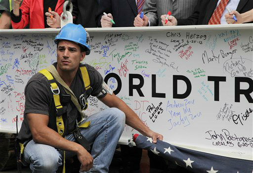 "<div class=""meta ""><span class=""caption-text "">An ironworker holds a furled American flag as officials autograph the ceremonial last beam before it is hoisted to the top of Four World Trade Center, Monday, June 25, 2012. The 72-floor, 977-foot tower is scheduled to open late next year. It's expected to be the first tower completed on the 16-acre site since the 9/11 attacks. (AP Photo/Mark Lennihan) (AP Photo/ Mark Lennihan)</span></div>"