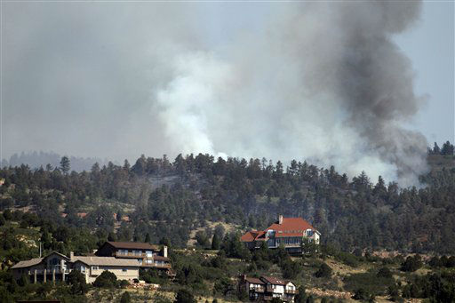 Fire burns behind homes on the Waldo Canyon wildfire west of Colorado Springs, Colo., on Monday, June 25, 2012. As many as 5,000 people are still evacuated from their homes because of the fire that began Saturday. &#40;AP Photo&#47;Ed Andrieski&#41; <span class=meta>(AP Photo&#47; Ed Andrieski)</span>