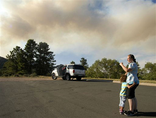 Susan Fox and her daughter Kaylehana, 4, watch the Waldo Canyon Fire burn near Colorado Springs, Colo., on Monday, June 25, 2012. The fire, one of at least a half-dozen wildfires in Colorado as of Monday, has blackened 5.3 square miles and displaced about 6,000 people since it started Saturday. &#40;AP Photo&#47;Bryan Oller&#41; <span class=meta>(AP Photo&#47; Bryan Oller)</span>