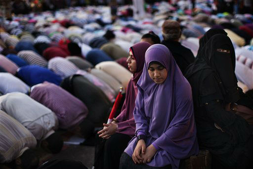 Egyptian women sit in Tahrir Square during prayer time, Cairo, Egypt, Monday, June 25, 2012. The new Egyptian president Mohammed Morsi moved first thing Monday morning into the office once occupied by his ousted predecessor Hosni Mubarak and started work on forming a government even before he had a clear picture of what he could do after the ruling military stripped most of the major powers from his post.&#40;AP Photo&#47;Bernat Armangue&#41; <span class=meta>(AP Photo&#47; Bernat Armangue)</span>