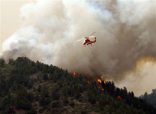 Flames of the Waldo Canyon Fire races down into western portions of Colorado Springs, Colo. on Tuesday, June 26, 2012. A helicopter tries to slow it down before it left a trail of destruction, burning homes and buildings in it&#39;s path.  Heavily populated areas in the fire&#39;s path have been affected.   &#40;AP Photo&#47;Bryan Oller&#41; <span class=meta>(AP Photo&#47; Bryan Oller)</span>