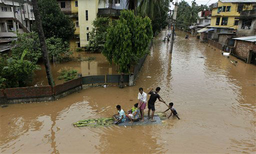 People use a raft made of banana plants to wade through flood waters in Gauhati, India, Tuesday, June 26, 2012. Flooding in the north eastern Assam state on Tuesday turned grim with most of the rivers breaching embankments and inundating new areas. Road links have been cut in many places and at least ten people have died according to local news reports. &#40;AP Photo&#47;Anupam Nath&#41; <span class=meta>(AP Photo&#47; Anupam Nath)</span>