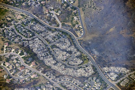 This aerial photo taken on Wednesday, June 27, 2012, shows burned homes in the Mountain Shadows residential area of Colorado Springs, Colo., that were destroyed by the Waldo Canyon wildfire. More than 30,000 have been displaced by the fire, including thousands who frantically packed up belongings Tuesday night after it barreled into neighborhoods in the foothills west and north of Colorado?s second-largest city. &#40;AP Photo&#47;John Wark&#41; <span class=meta>(AP Photo&#47; John Wark)</span>