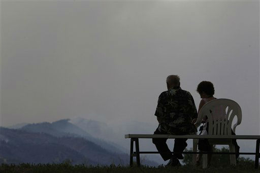 "<div class=""meta image-caption""><div class=""origin-logo origin-image ""><span></span></div><span class=""caption-text"">A couple watches a wildfire as it rolls through housing subdivisions in the mountains north and west of Colorado Springs, Colo., on Wednesday, June 27, 2012. The wildfire doubled in size overnight to about 24 square miles (62 square kilometers), and has so far forced mandatory evacuations for more than 32,000 residents. (AP Photo/David Zalubowski) (AP Photo/ David Zalubowski)</span></div>"