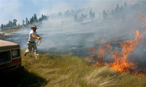 "<div class=""meta ""><span class=""caption-text "">Chris Kirchhevel rushes to spray another hot spot along the edge of a wildfire moving through the Dahl Ranch south of Roundup, Mont., on Wednesday, June 27, 2012. The fire has burned more than 18,000 acres and is still growing. (AP Photo/Matthew Brown) (AP Photo/ Matthew Brown)</span></div>"