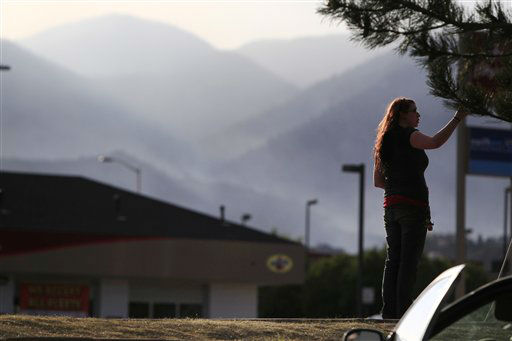 An unidentifed woman looks on as smoke envelopes ridges as a wildfire rolls through housing subdivisions in the mountains north and west of Colorado Springs, Colo., on Wednesday, June 27, 2012. The fire has forced the evacuation of more than 32,000 residents of the communities west of and now in Colorado Springs proper. &#40;AP Photo&#47;David Zalubowski&#41; <span class=meta>(AP Photo&#47; David Zalubowski)</span>