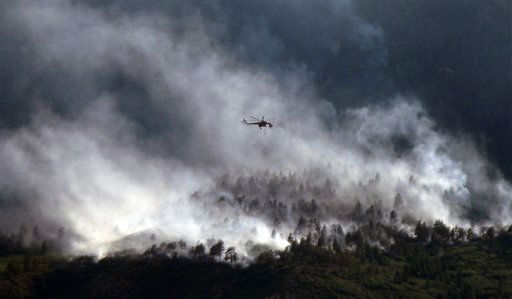 "<div class=""meta ""><span class=""caption-text "">A helicopters flies over as the Waldo Canyon Fire continues to burn Wednesday, June 27, 2012, in Colorado Springs, Colo. The wildfire doubled in size overnight to about 24 square miles (62 square kilometers), and has so far forced mandatory evacuations for more than 32,000 residents.  (AP Photo/Bryan Oller) (AP Photo/ Bryan Oller)</span></div>"
