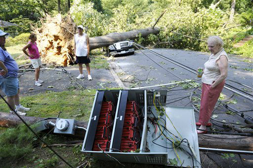 Marilyn Golias, right, looks at the remains of a utility pole which fell across the street from her house in Falls Church, Va., Saturday, June 30, 2012. Millions across the mid-Atlantic region sweltered Saturday in the aftermath of violent storms that pummeled the eastern U.S. with high winds and downed trees, killing at least 13 people and leaving 3 million without power during a triple-digit heat wave. &#40;AP Photo&#47;Cliff Owen&#41; <span class=meta>(AP Photo&#47; Cliff Owen)</span>