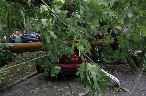 "<div class=""meta ""><span class=""caption-text "">Paul Berges, 16, takes a photograph of his neighbor's car crushed under fallen trees and telephone poles Saturday, June, 30, 2012, in Linwood, N.J. Severe thunderstorms packing heavy rain, lightning and strong winds that gusted up to 70 mph hit the state Saturday, knocking out power to hundreds of thousands and killing at least two. (AP Photo/Mel Evans) (AP Photo/ Mel Evans)</span></div>"