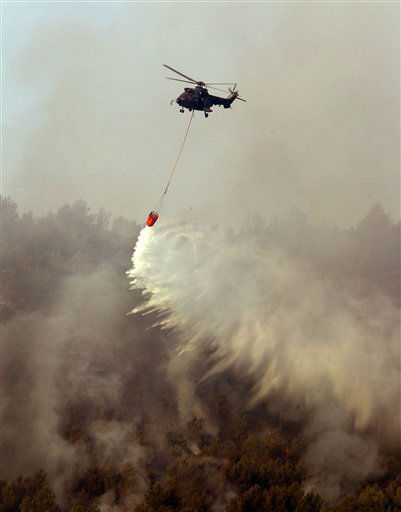 A helicopter tries to extinguish a wildfire in Altura, near Valencia, Spain, Monday, July 2, 2012. Over 1,000 firefighters are working in the regions of Valencia to put out the flames, but the task has been made more difficult due to strong winds and high temperatures of around 40 degrees celsius. &#40;AP Photo&#47;Alberto Saiz&#41; <span class=meta>(AP Photo&#47; Alberto Saiz)</span>
