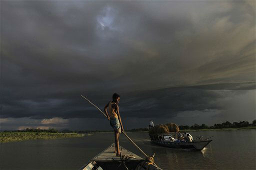 A boat carries flood relief materials as monsoon clouds surrounded the flood affected Gagalmari village in Assam state, India, Monday, July 2, 2012. The floods from monsoon rains in northeastern India killed dozens of people, with more than 2,000 villages inundated as rivers breached their banks, an official said Sunday. &#40;AP Photo&#47;Anupam Nath&#41; <span class=meta>(AP Photo&#47; Anupam Nath)</span>
