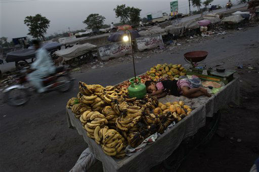 A Pakistani child, Shahryar Ameer, 2, the son of a fruit vendor, sleeps on his father&#39;s cart, on a roadside on the outskirts of Islamabad, Pakistan, early Monday, July 2, 2012. &#40;AP Photo&#47;Muhammed Muheisen&#41; <span class=meta>(AP Photo&#47; Muhammed Muheisen)</span>