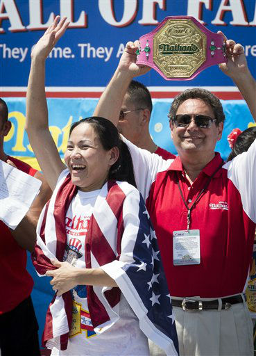 Sonya &#34;The Black Widow&#34; Thomas accepts her trophy after she wins  Nathan&#39;s Famous Women&#39;s Hot Dog Eating World Championship, Wednesday, July 4, 2012, at Coney Island, in the Brooklyn borough of New York.  Thomas beat her own record by gobbling down 45 hot dogs and buns in 10 minutes to win the women&#39;s competition at the annual Coney Island contest.  &#40;AP Photo&#47;John Minchillo&#41; <span class=meta>(AP Photo&#47; John Minchillo)</span>