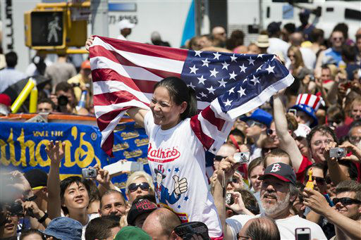Sonya &#34;The Black Widow&#34; Thomas is carried through the crowds after breaking her world record during the Nathan&#39;s Famous Women&#39;s Hot Dog Eating World Championship, Wednesday, July 4, 2012, at Coney Island, in the Brooklyn borough of New York. Thomas won her second consecutive women&#39;s competition with 45 downed hot dogs. &#40;AP Photo&#47;John Minchillo&#41; <span class=meta>(AP Photo&#47; John Minchillo)</span>