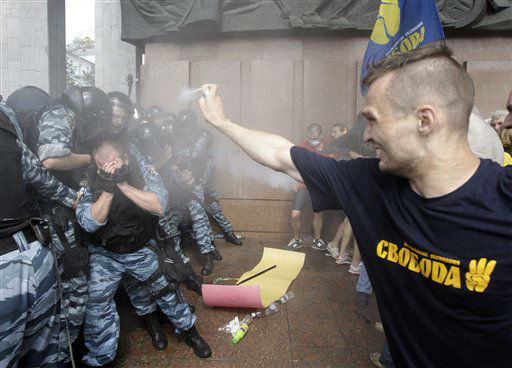 Opposition protesters spray tear gas against riot police in front of the Ukrainian House in central Kiev, Ukraine, Wednesday, July 4, 2012. Opposition activists have clashed with riot police  during a protest against a controversial bill that would allow the use of Russian in official settings in Russian-speaking regions. &#40;AP Photo&#47;Efrem Lukatsky&#41; <span class=meta>(AP Photo&#47; Efrem Lukatsky)</span>