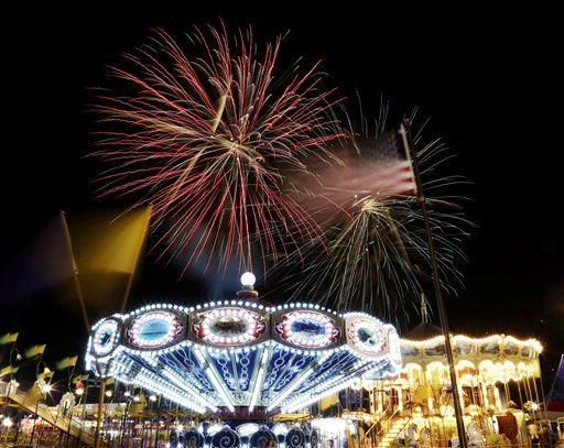 A United States flag waves next to carnival rides as fireworks burst in the air during the Fourth of July Independence Day show at State Fair Meadowlands, Tuesday, July 3, 2012, in East Rutherford, N.J. &#40;AP Photo&#47;Julio Cortez&#41; <span class=meta>(AP Photo&#47; Julio Cortez)</span>
