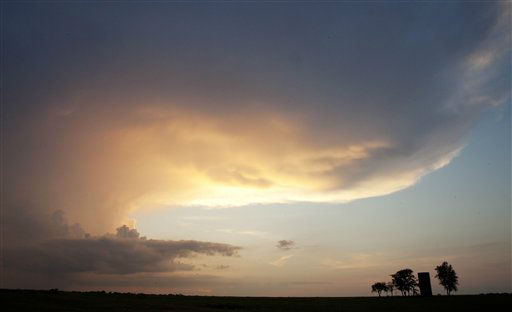 An isolated thunderstorm moves over trees and silo on a farm near Wichita, Kan., Sunday, July 8, 2012. A cold front dropped high temperatures into the mid 90s after moving through overnight. &#40;AP Photo&#47;Orlin Wagner&#41; <span class=meta>(AP Photo&#47; Orlin Wagner)</span>