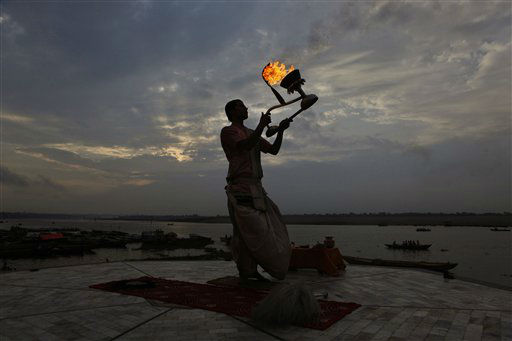 A Hindu priest rotates a traditional oil lamp in circular movements as he performs morning prayers on the banks of the River Ganges in Varanasi, India, Monday, July 9, 2012. About 40,000 devout Hindus bathe each day in the Ganges at Varanasi, one of the holiest Hindu sites in India. &#40;AP Photo&#47;Rajesh Kumar Singh&#41; <span class=meta>(AP Photo&#47; Rajesh Kumar Singh)</span>