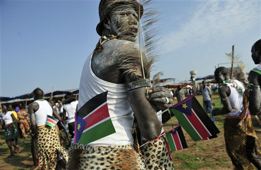 A man holds South Sudanese flags as he prepares to dance at the country&#39;s anniversary celebrations, at the John Garang mausoleum in Juba, South Sudan, Monday, July 9, 2012. The world&#39;s newest nation, South Sudan, is celebrating its first birthday and while the largest achievement over the last year was avoiding a return to all-out war with Sudan, the south has seen its economy crippled after it shut down its oil industry and thousands of refugees are streaming into the country every week to avoid violence on Sudan&#39;s side of the border. &#40;AP Photo&#47;Shannon Jensen&#41; <span class=meta>(AP Photo&#47; Shannon Jensen)</span>