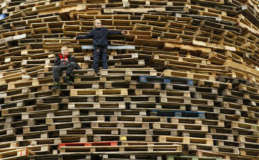 Children stand on a massive bonfire in the Shankill Estate in West Belfast, Northern Ireland, Tuesday, July 10, 2012. Thousands of bonfires have been built in Protestant areas across Northern Ireland for the annual July 11 bonfire night where they celebrate the 1690 battle of the Boyne were the Protestant King William of Orange defeated the Catholic King James.  &#40;AP Photo&#47;Peter Morrison&#41; <span class=meta>(AP Photo&#47; Peter Morrison)</span>