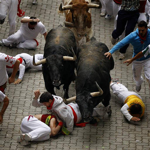 Revelers run and fall in front of Fuente Ymbro&#39;s ranch fighting bulls during the running of the bulls of the San Fermin festival, in Pamplona, Spain, Wednesday, July 11, 2012. &#40;AP Photo&#47;Daniel Ochoa de Olza&#41; <span class=meta>(AP Photo&#47; Daniel Ochoa de Olza)</span>