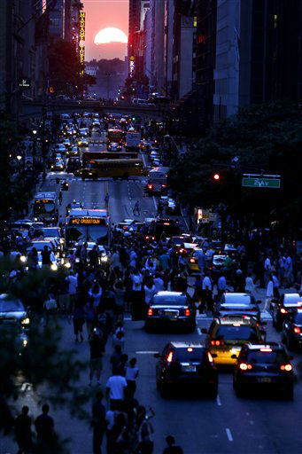 "<div class=""meta ""><span class=""caption-text "">People stand in the middle of 42nd Street in New York's Manhattan borough as the sun sets through the middle of the buildings during a phenomenon known as Manhattanhenge, Wednesday, July 11, 2012. Manhattanhenge, sometimes referred to as the Manhattan Solstice, happens when the setting sun aligns with the east-to-west streets of the main street grid. The term references Stonehenge, at which the sun aligns with the stones on the solstices in England. (AP Photo/Julio Cortez) (AP Photo/ Julio Cortez)</span></div>"