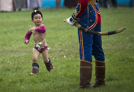 A Mongolian boy in costume runs past a member of guard of honor during the Naadam Festival in Ulan Bator, Mongolia Wednesday, July 11, 2012. Mongolians celebrate the anniversary of Genghis Khan&#39;s march to world conquest on July 11 with the annual sports festival featuring traditional Mongolian events including wrestling, archery, and horse racing. &#40;AP Photo&#47;Andy Wong&#41; <span class=meta>(AP Photo&#47; Andy Wong)</span>