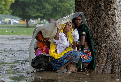 Women sit under a plastic sheet to shelter themselves from the rain in New Delhi, India, Thursday, July 12, 2012. The monsoon rains which usually hit India from June to September are crucial for farmers whose crops feed hundreds of millions of people. &#40;AP Photo&#47;Saurabh Das&#41; <span class=meta>(AP Photo&#47; Saurabh Das)</span>