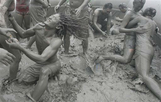 Tourists play with the mud during the 15th annual mud festival on Daecheon Beach in Boryeong, South Korea, Sunrday, July 15, 2012. The festival features mud wrestling, mud sliding and mud king contest. &#40;AP Photo&#47;Ahn Young-joon&#41; <span class=meta>(AP Photo&#47; Ahn Young-joon)</span>