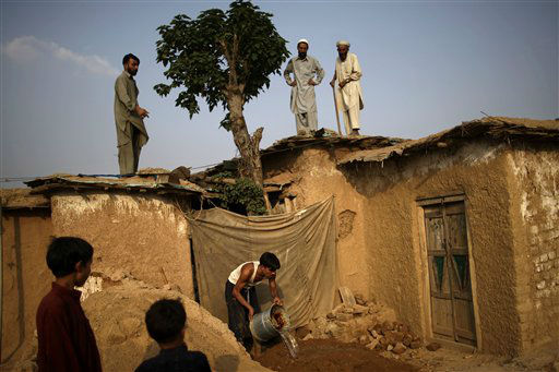 A Pakistani man pours water on mud, while he and other family members work on fixing the rooftop of their home, in a poor neighborhood on the outskirts of Islamabad, Pakistan, Monday, July 16, 2012. &#40;AP Photo&#47;Muhammed Muheisen&#41; <span class=meta>(AP Photo&#47; Muhammed Muheisen)</span>