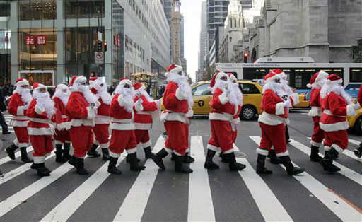 Volunteers of America Santas ring their bells as the cross a street in Fifth Ave. during their 110th annual Sidewalk Santa Parade, in New York,  Friday, Nov. 23, 2012. The donations they raise are used for a holiday food voucher program for needy residents. &#40;AP Photo&#47;Richard Drew&#41; <span class=meta>(AP Photo&#47; Richard Drew)</span>