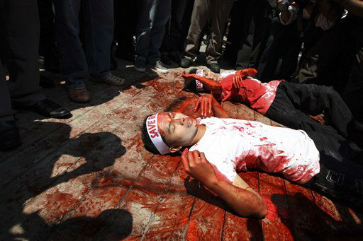 Covered in mock blood, Muslim protesters perform a die-in during a rally outside the embassy of Myanmar in Jakarta, Indonesia, Thursday, Aug. 9, 2012. Dozens of people staged the rally calling for an end to the violence against ethnic Rohingya Muslims in Rakhine State of Myanmar. &#40;AP Photo&#47;Dita Alangkara&#41; <span class=meta>(AP Photo&#47; Dita Alangkara)</span>